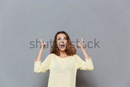 Amazed woman covered mouth with hand and showing copyspace Stock photo © deandrobot