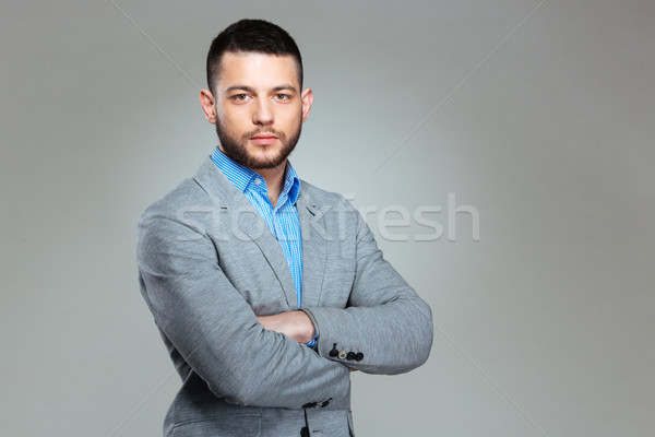 Serious businessman standing with arms folded Stock photo © deandrobot