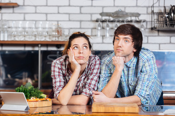 Stock photo: Pensive couple thinking on the kitchen
