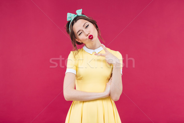 Pretty playful pinup girl winking and sending a kiss Stock photo © deandrobot