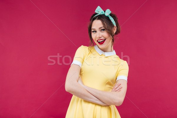 Cheerful lovely pinup girl in yellow dress standing and smiling Stock photo © deandrobot