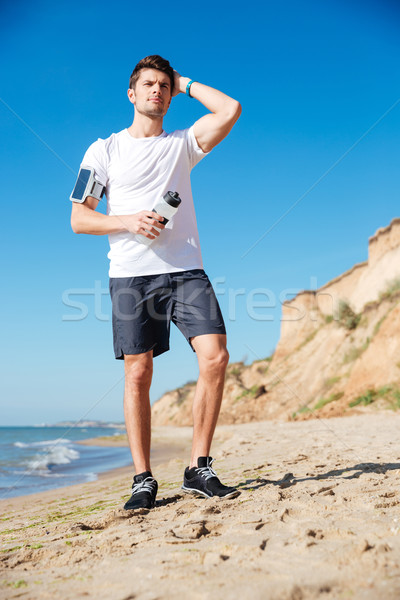 Attractive young sportsman with bottle of water on the beach Stock photo © deandrobot