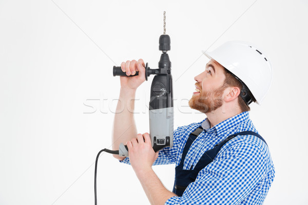 Smiling young builder in helmet using drill and looking up Stock photo © deandrobot