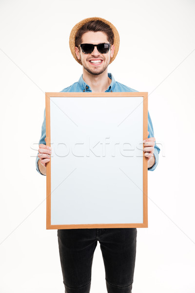 Stock photo: Cheerful young man in hat and sunglasses holding blank whiteboard
