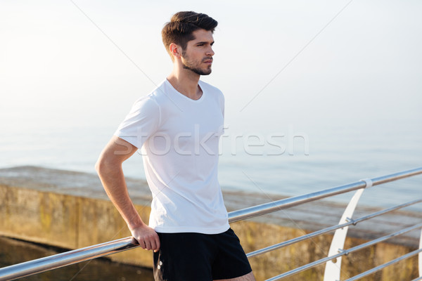 Serious young sportsman standing on pier Stock photo © deandrobot