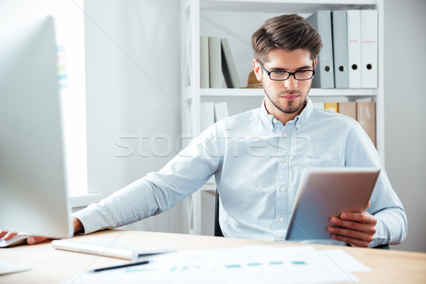 Pensive businessman sitting and using tablet computer in office Stock photo © deandrobot