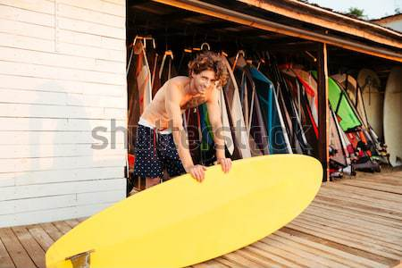 Young smiling professional surfer holding surf board Stock photo © deandrobot