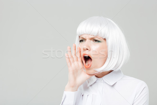 Pretty young woman shouting and calling for somebody Stock photo © deandrobot