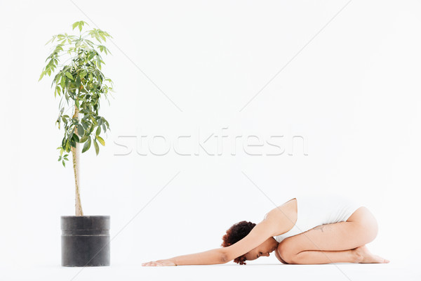 Peaceful african american young woman doing relaxing yoga exercises Stock photo © deandrobot