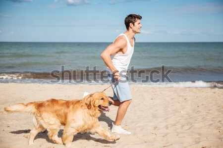 Man jogging and having fun with dog on the beach Stock photo © deandrobot