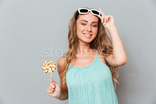 Sorridente mulher jovem óculos de sol doce pirulito primavera Foto stock © deandrobot