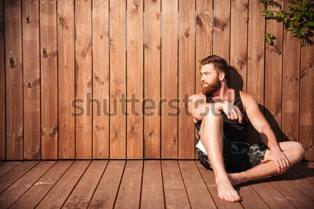Beautiful young woman in bikini eating watermelon over wooden background Stock photo © deandrobot