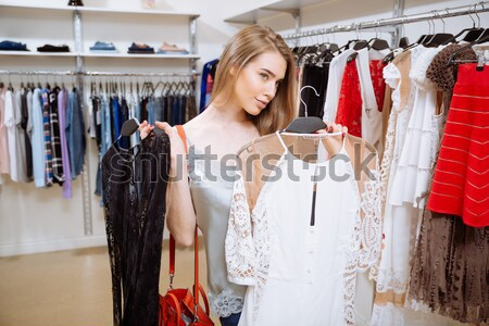 Smiling young woman holding two dresses in clothing shop Stock photo © deandrobot