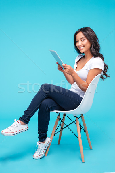 Woman using tablet pc computer while sitting on the chair Stock photo © deandrobot