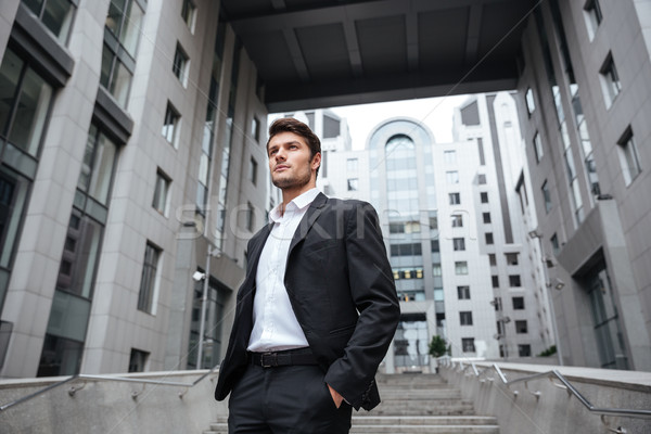 Stock photo: Handsome young businessman in suit standing near business center