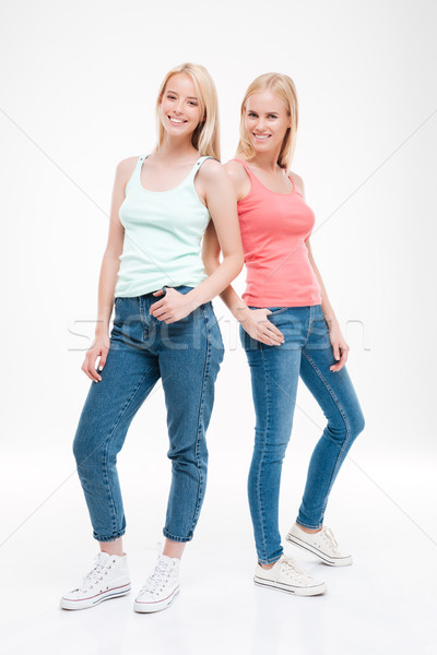 Two young women dressed in t-shirts and jeans posing Stock photo © deandrobot