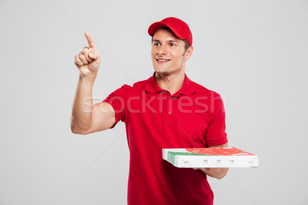 Pizza delivery man looking away Stock photo © deandrobot