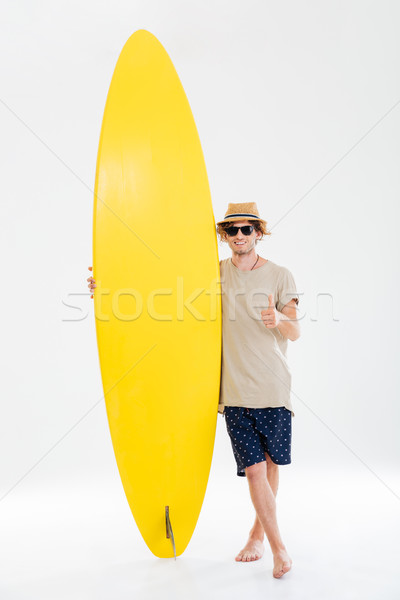 Man in sunglasses and hat showing thumbs up holding surfboard Stock photo © deandrobot