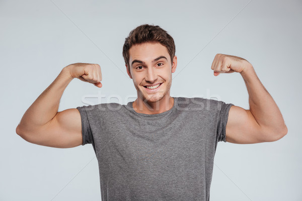 Portrait souriant homme biceps isolé gris Photo stock © deandrobot