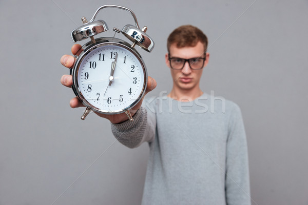 Man in glasses showing clock Stock photo © deandrobot