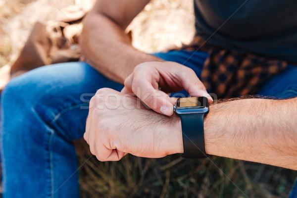 Close up portrait of a man using smartwatch outdoors Stock photo © deandrobot