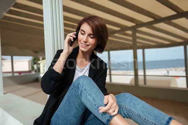 Happy woman sitting and talking on cell phone in gazebo Stock photo © deandrobot