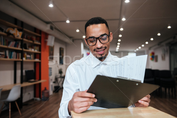Happy african businessman looking at notepad. Coworking. Stock photo © deandrobot