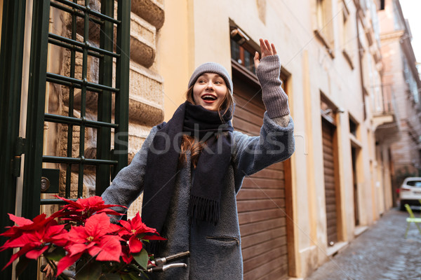 Incredible young caucasian lady waving to friends outdoors Stock photo © deandrobot