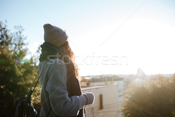 Beautiful young woman enjoying the view on sunset in city Stock photo © deandrobot