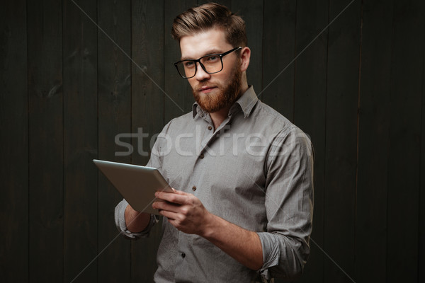 Man in eyeglasses holding tablet computer and looking away Stock photo © deandrobot