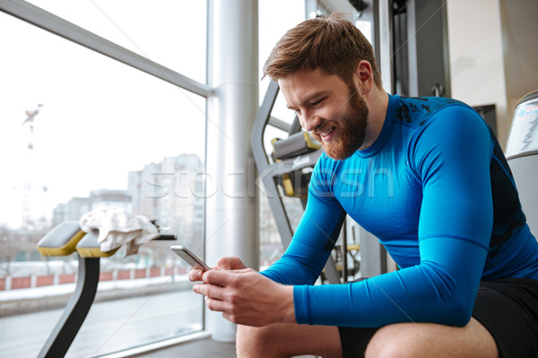 Cheerful young sportsman sitting in gym and looking at phone. Stock photo © deandrobot
