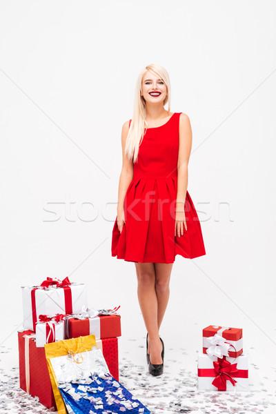Nő vörös ruha áll halom ajándékok boldog Stock fotó © deandrobot