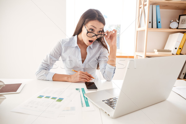 Businesswoman dressed in white shirt shocking when open a laptop Stock photo © deandrobot