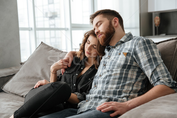 Loving couple sitting on sofa and sleeping indoors. Stock photo © deandrobot
