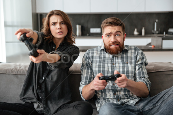 Loving couple in kitchen playing games with console. Stock photo © deandrobot