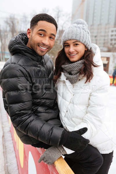 Young smiling loving couple skating at ice rink outdoors. Stock photo © deandrobot