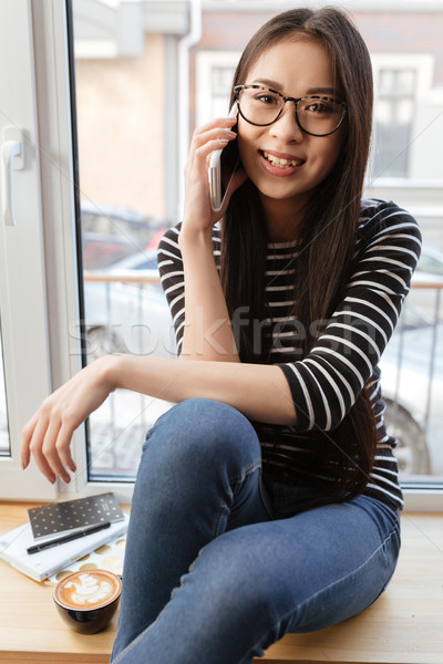 Vertical image of Happy Asian woman talking phone on windowsill Stock photo © deandrobot