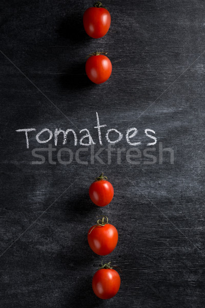Tomatoes over dark background Stock photo © deandrobot
