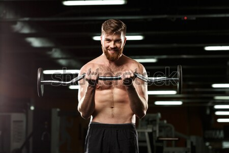 Stock photo: Handsome sports man make sport exercises with dumbbells