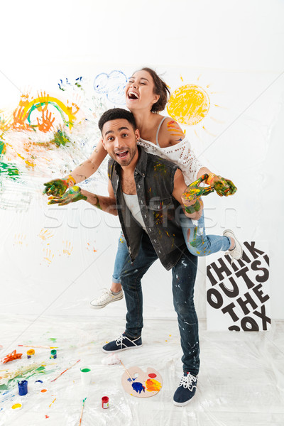 Stock photo: Cheerful man holding girlfriend on back and painting by hands