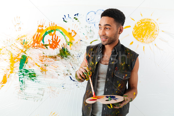 Stock photo: Handsome african american young man holding palette and paintbrush