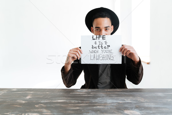African man hiding behind sheet of paper with words Stock photo © deandrobot