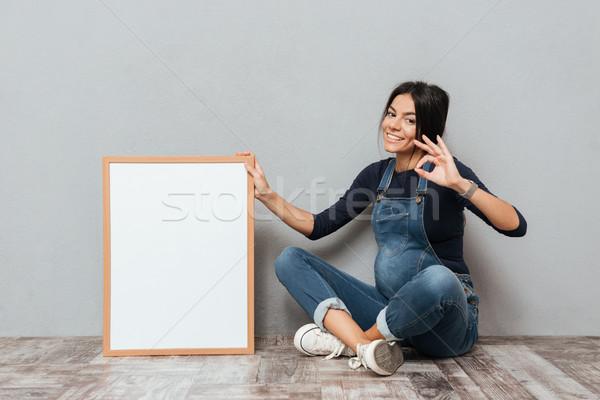 Gelukkig zwangere dame vergadering vloer tonen Stockfoto © deandrobot