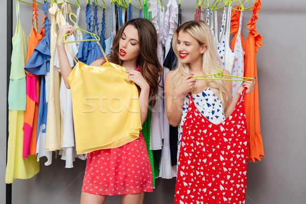 Kobiet patrząc shirt uśmiechnięty młodych kobiet wieszak Zdjęcia stock © deandrobot