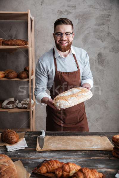 Stock photo: Cheerful young man baker standing at bakery holding bread