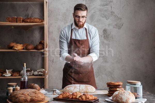 Fiatal koncentrált szakállas férfi visel szemüveg Stock fotó © deandrobot