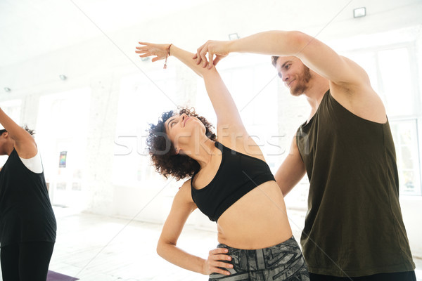 Maschio yoga istruttore aiutare donna fitness Foto d'archivio © deandrobot