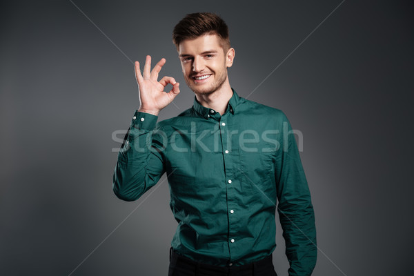 Happy man posing over grey background showing okay gesture. Stock photo © deandrobot