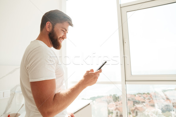 Side view of bearded man using his smartphone Stock photo © deandrobot