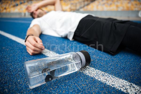 Kimerült fiatal sportoló üveg víz stadion Stock fotó © deandrobot
